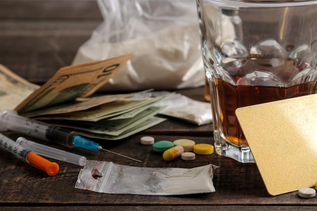 갈색 나무 테이블에 알코올, 담배, 마약을 포함한 다양한 중독성 약물. 마약 중독 개념