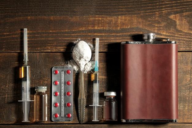 갈색 나무 테이블에 알코올, 담배, 마약을 포함한 다양한 중독성 약물. 위에서 보기