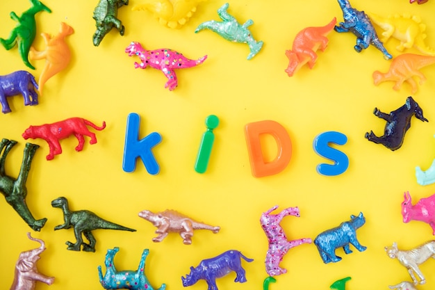 Various animal toy figures background with the word kids