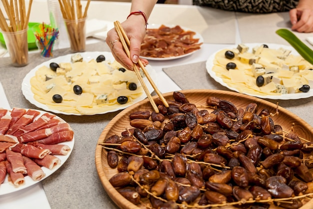 Various appetizers of cheese, meat and dates for a buffet