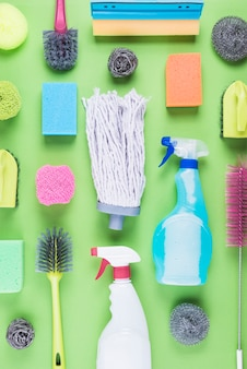 Various assorted cleaning equipments on green background
