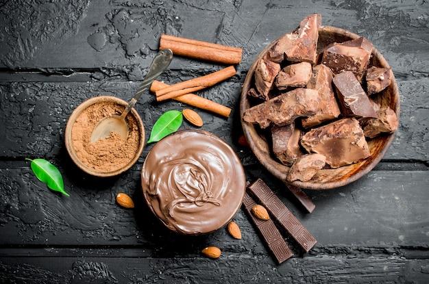 Различный ассортимент шоколада с пастой. на черном деревенском столе.
