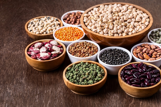 Various assortment set of indian legumes in bowls on wooden background with copyspace.