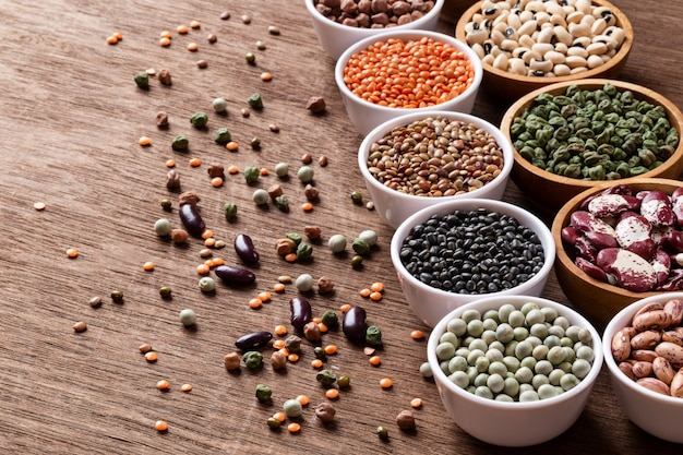 Various assortment set of indian legumes in bowls on wooden background