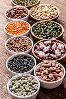 Various assortment set of indian legumes in bowls on wooden background.