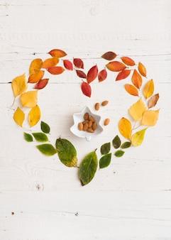ハート型のさまざまな秋の色とりどりの葉と白い木製の背景にアーモンドナッツとボウル