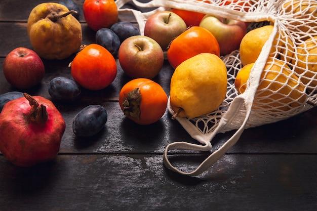 Различные осенние фрукты в сетчатом мешке на темном деревянном фоне.
