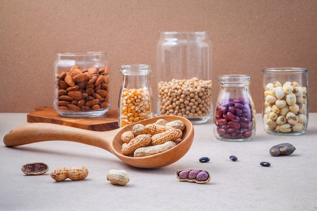 Various beans and nuts in the glass on brown background.