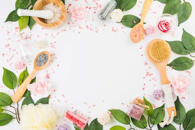 Various beauty products with leaves forming frame on white background