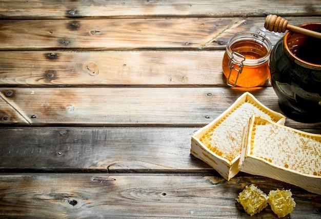 Различный пчелиный мед. на деревянном столе.