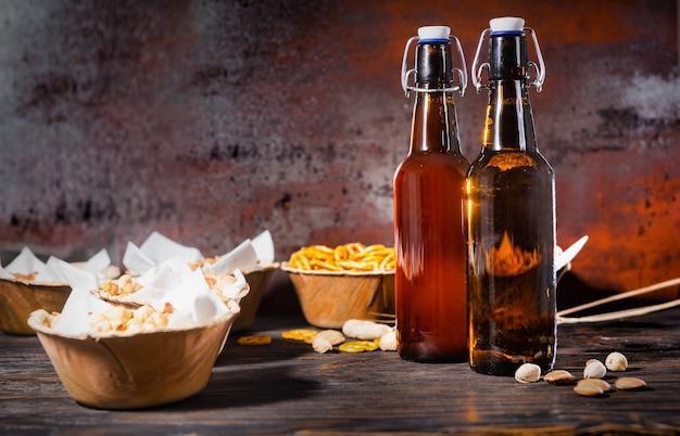 暗い木製の机の上の2つのビール瓶の近くに、ピスタチオ、小さなプレッツェル、ピーナッツなどのプレートに入ったさまざまなビールスナック。食品および飲料の概念