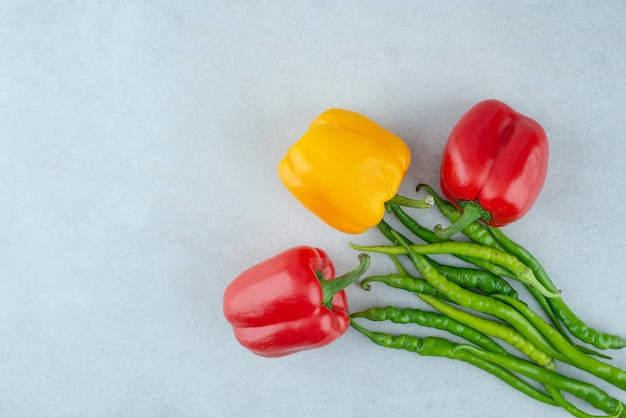 Various bell and chili peppers on blue surface.