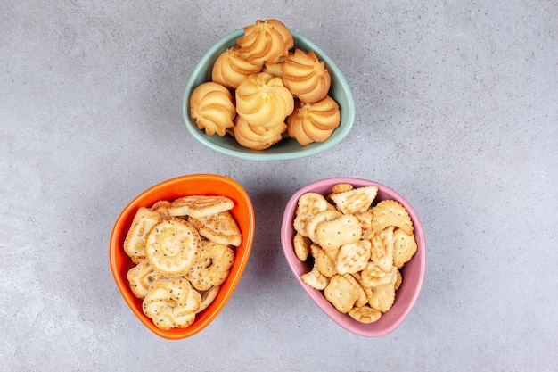 Various biscuits and cookies in colorful bowls on marble background. high quality photo