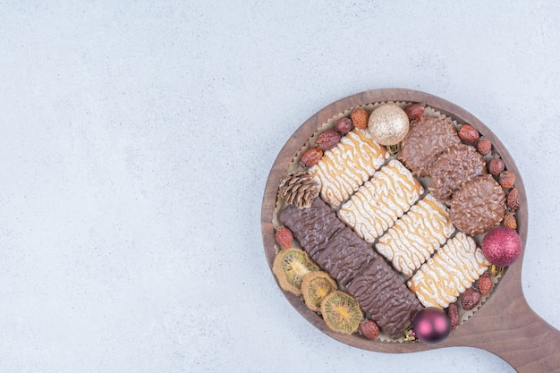 Various biscuits, dried fruits and christmas baubles on wooden board.