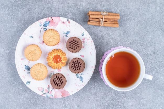熱いお茶のカップとプレート上の様々なビスケット