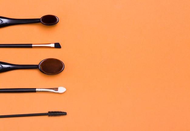 Various black brushes on an orange background
