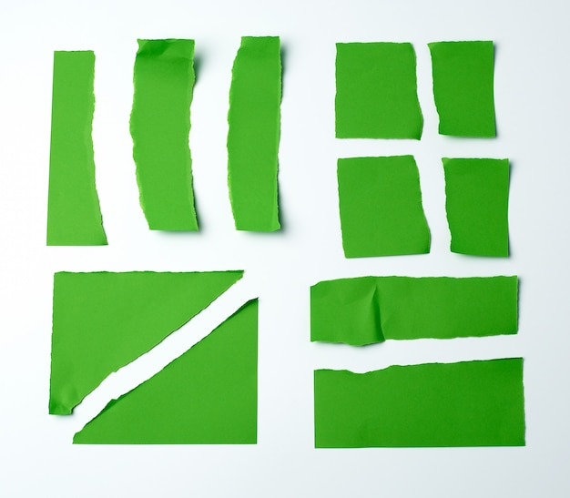Various blank pieces of green paper on white surface,