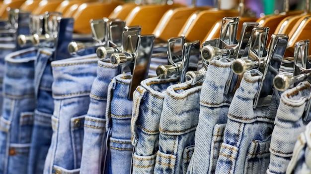 Различные синие джинсы на вешалке в магазине одежды