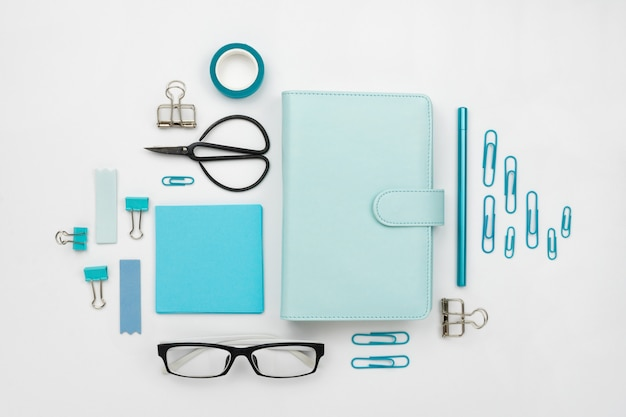 Various blue stationary and office tools and accessories knolled together on white: planner, pens, pencils, clips, glasses, scissors, etc. flatlay