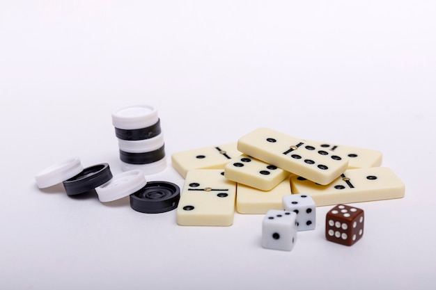 Various board games chess, dice and dominoes on white