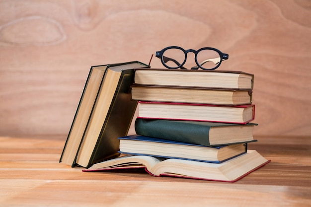 Various books with spectacles on a table
