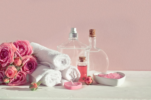 Various bottles of cosmetics and cotton towels on a pink surface with roses