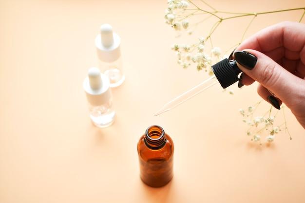 女の子の手ピペットの化粧品オイルの様々なボトル。老化防止のためのおしゃれな化粧品。フラット横たわっていた、トップビュー。