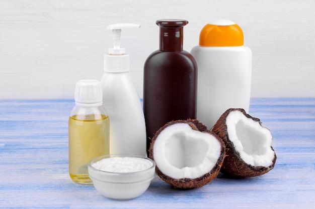 白い背景の上の青い木製のテーブルの上の新鮮なココナッツの横にココナッツ抽出物と化粧品の様々なボトル
