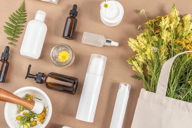 Различные бутылки, тубы, банка с косметикой, полевые цветы в эко-текстильном мешке, ступка с пестиком на бежевом фоне. понятие натуральной травяной органической косметики, гомеопатической косметологии. вид сверху .