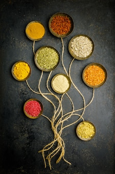 Various bowls of spices over dark table