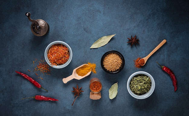 Various bowls and spoons of turkish spices on  dark blue background. top view, copy space and flat lay