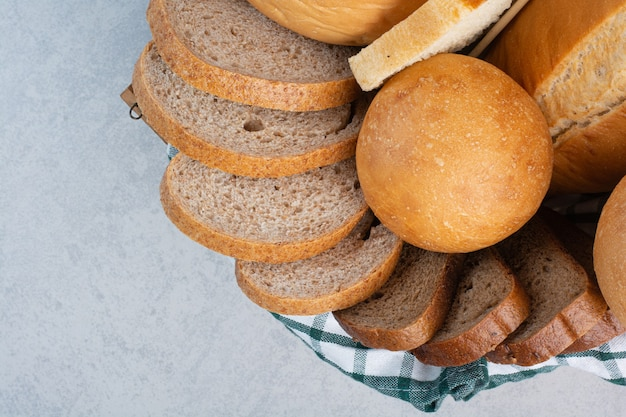 Various bread in basket on marble background. high quality photo