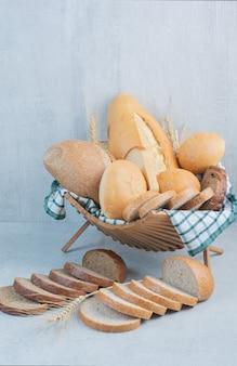 大理石の背景にバスケットの様々なパン。高品質の写真