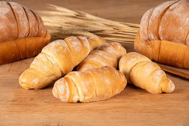 Различный хлеб на деревянном столе с пшеничной соломой на заднем плане