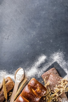 Various bread set. many different wheat, grain and rye bread with ears of rye and wheat, flour and baker's tools on a white wooden background