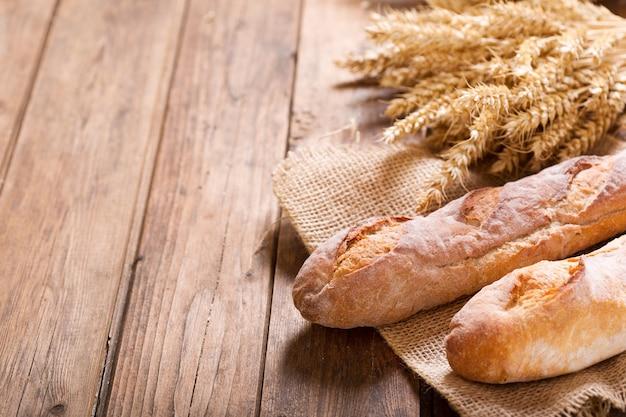 木製のテーブルに小麦の穂を持つ様々なパン