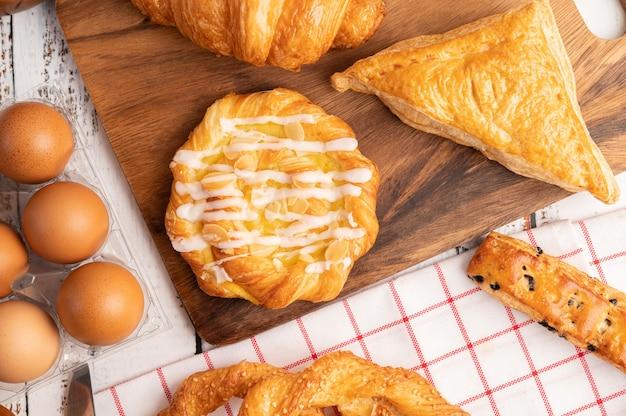 Различный хлеб и яйца на красно-белой ткани.