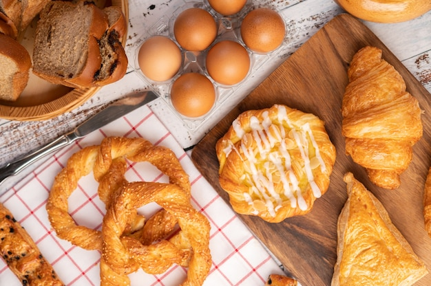 Various breads and eggs on red white cloth.