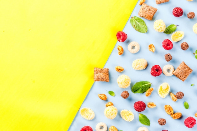 Various breakfast cereal, raspberries and mint on blue yellow