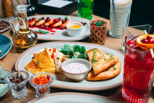 Various breakfast dishes are served on the table in the restaurant