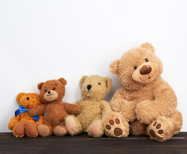 Various brown teddy bears are sitting on a brown wooden table