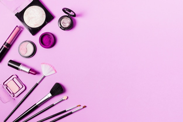 Various brushes and cosmetics in purple tint