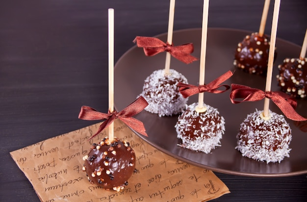 Various cake pops decorated with dark chocolate on a brown background