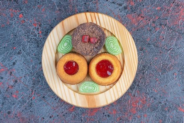 Vari dolci e marmellate su un piatto di legno sul tavolo astratto.