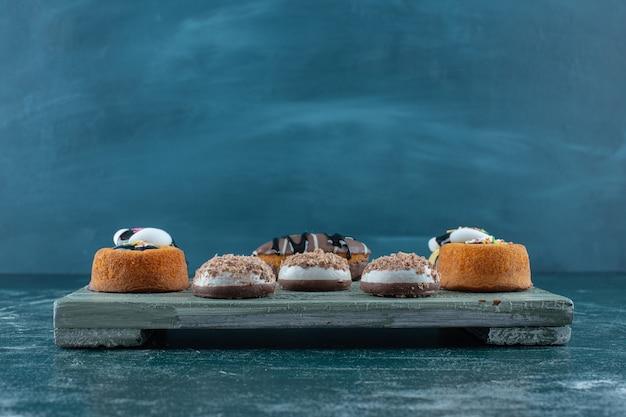 青い背景のボード上の様々なケーキ。高品質の写真