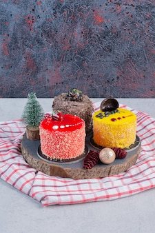 クリスマスの飾りと暗いボード上の様々なケーキ。