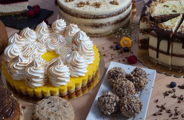 木製のテーブルにさまざまなケーキ。お祝い用のケーキの品揃え。お誕生日