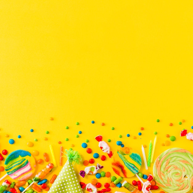 Various candies and party hat at the bottom of yellow background
