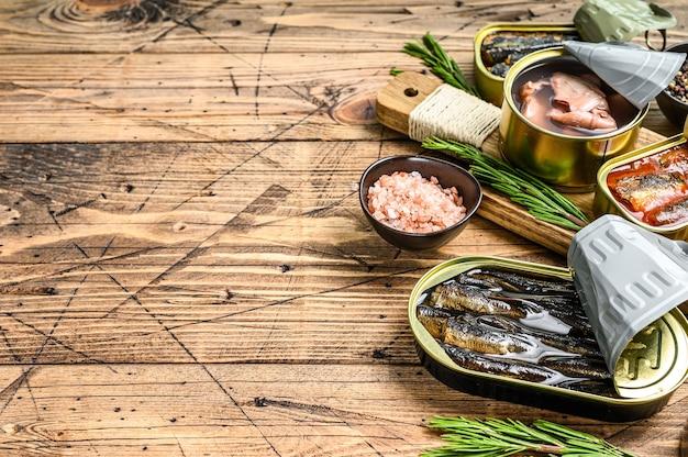金属缶に入った様々な魚介類の缶詰。木製の背景。上面図。