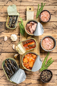 Various canned  fish and seafood in a metal cans. wooden background. top view.